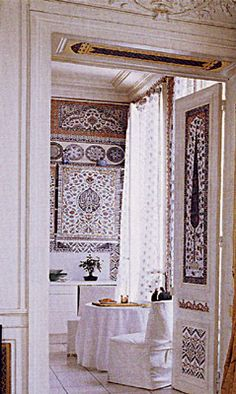 The white trim and white curtains are only enhanced by the intricate pattern of the wallpaper from Iksel