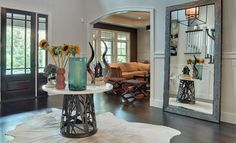 Artistic Foyer Decorations with Vases and Other Ornaments on Top of a Table at The Entry and Large Shabby Mirror