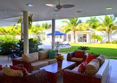 Completando a decoração do alpendre, um lounge com poltronas e móveis em fibra natural, ideais para áreas externas, é o local ideal para divertidas conversas com os amigos nas tardes de férias na praia.
