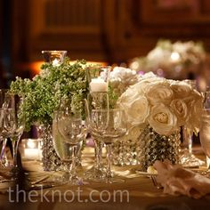 Low, crystal vases showcase bunches of white roses and sweet peas.