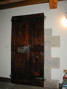 Vista anteriore del portone antico, che in fase di restauro appare con la vernice verde, collocato in un'interno e restaurato.
