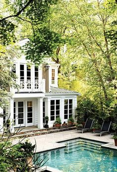 The trees, pool, and second-floor porch make for a scenic backyard.