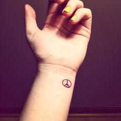 small peace tattoo on wrist