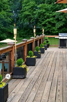 Black railing mixed with wood and black planters