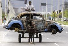 Een Braziliaan transporteert de resten van een uitgebrande Volkswagen Kever op paard en wagen in Rio de Janeiro.