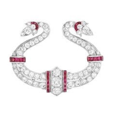 Art Deco Platinum, Diamond and Ruby Brooch. The pierced stylized scroll topped by 3 old European and old-mine cut diamonds approximately 1.00 ct., set throughout with 54 old European and 2 single-cut diamonds approximately 3.70 cts., accented by 30 rectangular-shaped and tapered baguette rubies, circa 1925, approximately 12.7 dwts.