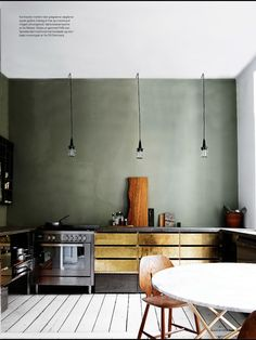 Great gray plaster wall, brass cabinets, white painted floor... minimal, rustic