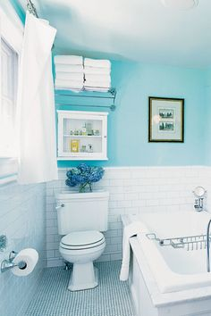 Bring color into a bathroom not only through a bright wall hue, as seen here in this small space, but also through fresh flowers, like blue hydrangeas—they'll provide a pleasing pick-me-up every morning.