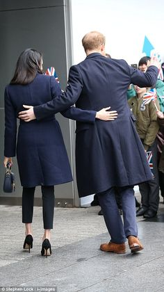Harry and Meghan put a hand on each other's backs as they wave to the crowds during the wa...