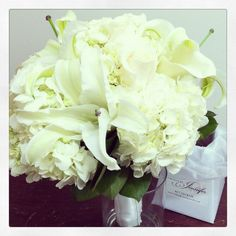 Bridal bouquet - all white. Hydrangeas,calla lilies, lilies and roses. Wrapped with white satin ribbon.