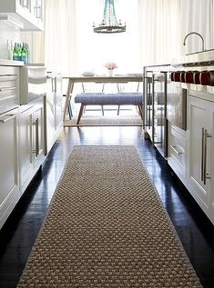 A sisal runner rug warms up the dark chocolate hardwood floors of this modern kitchen (without adding any new clashing colors!).