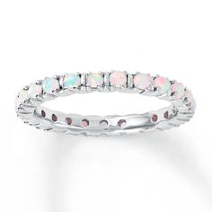This stackable ring is made of sterling silver and wrapped in round lab-created opals. The band is 2.5mm wide.