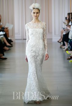 Brides.com: . Long-sleeve corded lace sheath with a ruffled back and high, sheer neckline, Oscar de la Renta