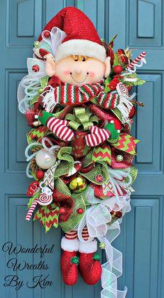 Ce lutin est unique en son genre et est prêt à répandre une joie des fêtes ! Ce butin mesure 32 pouces de longueur et 15 pouces de diamètre. Doté d'un Lutin Adorable, présente, pics de menthe poivrée, ornements de gros pois, 4 types de ruban et bien plus ! Cette couronne est sûre d'apporter un sourire à votre visage, heureusement salutations amis et votre famille que vous leur souhaiter la bienvenue dans votre maison cette saison de vacances.  ** Il est recommandé de conserver cette couronne…