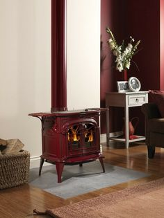 Woodstove, red enamel finish, white wall behind, simple square slate (?) hearth flush with hardwood floors surrounding it.