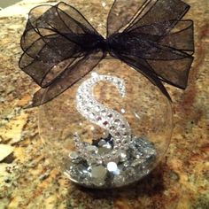 Clear ornament,srcap booking letter,silver acrylic stones, small black jewerly stones, black ribbon and your done... Great gift idea.