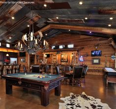Very large garage turned into a man cave with a pool table, full bar, shuffle board table and a Game of Thrones chandelier. Like the rustic touch on the ceiling. #gameofthrones #man #garagemancave