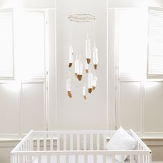 white nursery. DIY feather mobile. Gold-dipped feathers. gender neutral nursery. pretty nursery. interior design. baby room. nursery DIY to try.