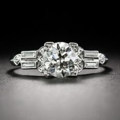 A big, bright and shining European-cut diamond, weighing 1.41 carats, presents even larger from within its four-cornered setting in this stunning and sophisticated Art Deco engagement ring, handcrafted in platinum - circa 1930. The distinctive and striking shoulders are each set with a pair of straight baguette diamonds embellished with diamond-shaped bright-cut accents leading to a sleek, soft knife-edge ring shank. An original vintage dazzler. Currently ring size 8 1/4.