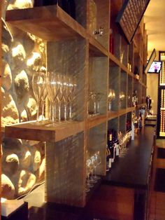 Back lighting on stone wall with rustic shelving makes a dramatic bar backdrop - would look really cool with brick wall