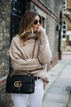 Emma Hill wears Beige chunky sweater, white skinny jeans medium black leather Gucci Marmont Matelasse bag, tan belt, Round gold metal frame Rayban sunglasses