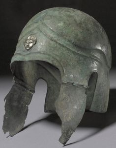 Chalcidian helmet, 5th century B.C. Ornamented with a silver satyr's head, the cheek-pieces may not belong to the helmet, but they are ancient and of the appropriate type British museum