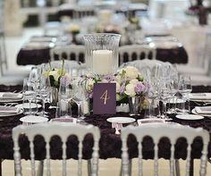 Square tables feature low arrangements of purple and white roses around a taller glass hurricane.
