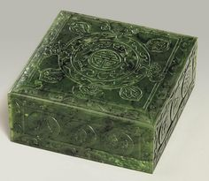 A SPINACH-GREEN JADE SQUARE BOX AND COVER 19TH CENTURY The top of the cover is delicately carved with a shou-character medallion, surrounded by two confronting kui-dragons and four mythical beasts. The sides of the cover are decorated with roundels of the Twelve Ornaments. The stone is of a deep green tone with darker and paler speckling throughout.