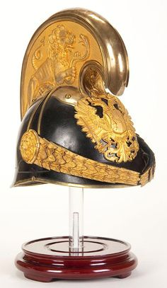 AN AUSTRIAN MODEL 1905 DRAGOON OFFICER'S HELMET. Black leather covered metal body, and high brass comb with lion embossed sides, gold washed eagle plate and chin scales.Jackson's International Auctioneers and Appraisers Military Fashion, Military Style, Helmet Armor, Imperial Army, Holy Roman Empire, Austro Hungarian, Gold Wash, Plaid Fashion, Leather Cover