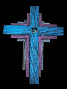 Made from reclaimed cedar, this cross is three layers, each 5/8 thick. The aged detail in the wood makes this an incredible piece. The top layer is distressed in Desert Turquoise, the next is distressed in a Rose color, and the third layer is washed in silver. The center is topped with a piece of silver and turquoise jewelry, with red, yellow and green crystal highlights. Complete with a hanger for your wall.  The top layer of the cross measures 12 1/4 X 9 1/4 X 1 3/8. Eac...
