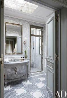 In the master bath, hand-carved details distinguish a custom-made vanity; the sink fittings and door hardware are by P. E. Guerin, and the marble-mosaic floor tile is by Smith for Ann Sacks | archdigest.com