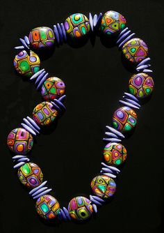 Polymer necklace by Carol Simmons. I've always loved the retro pattern, and this necklace has such gorgeous, shimmery colors.