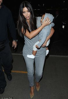 It's a match: Kim Kardashian and North West wear strikingly similar tops as they arrive at...