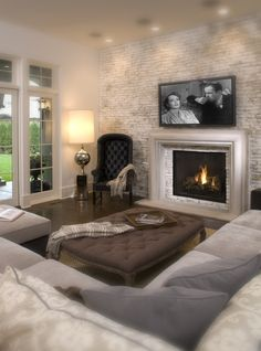 This is the exact set up I want in my living room! I want the focus point to be the fireplace, and the TV can go above it. Then do a coffee table and either two couches facing each other or something like this!