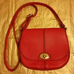 """NWOT Fossil Leather Crossbody Messeng./Saddle bag AuthenticNWOT Fossil red leather cross-body messager/saddle bag/purse.Fully lined. Flap-over entry. Buckle adjustable crossbody strap is made of leather on one side and cloth on the other side.Twist lock flap closure. Decorative hardware accents. 50"""" long strap. Accent stitching. Four pockets inside the flap, one of which has a zipper closure. Another pocket on the back of the bag w/zipper closure. Inside this pocket, there are 6 credit card…"""