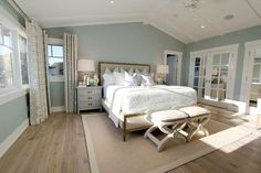 Steely light blue bedroom walls, wide-plank rustic wood floors, patterned curtains, lots of light, vaulted planked ceiling.: