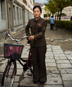 Another lady in uniform poses with her bike, a popular mode of transport in North Korea