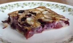 Slice of gluten-free cherry clafouti with sorghum flour on dessert plate, view from side.