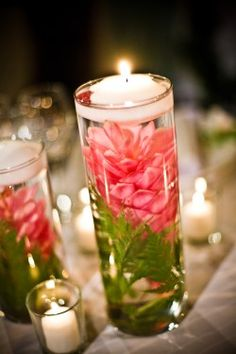 Flowers in water w candle in vase.