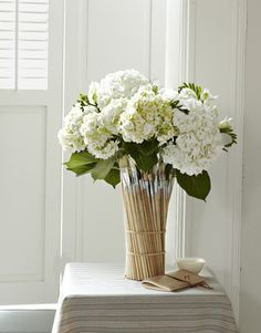 "Blogger Camilla Fabbri gives used paintbrushes a new lease on life with this fanciful centerpiece. ""I love the way the colorful bristles look,"" says Fabbri, an Evanston, Illinois, artist, ""and the whole thing takes just minutes."" Simply space two rows of plain rubber bands around a tall, cylindrical vase, then tuck brushes (Fabbri used about 40) inside the bands until the tools completely surround the vessel.   - CountryLiving.com"