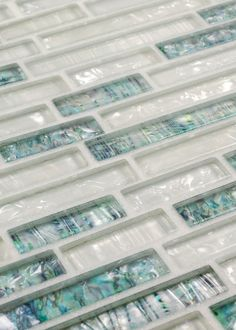 Pearl Glass Mosaic Tile White Linear Blend is made of clear glass and coated with a unique color palette, which recreates the look of a mother of pearl but with much more depth. The tiles are mesh mou