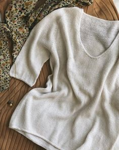 The Cumulus Tee is worked in stockinette stitch and has a rounded V-neck in the front. The sleeves are elbow length, and all edges are finished in i-cord. The Cumulus Tee requires no finishing work at the end. I Cord, Sport Weight Yarn, Classic Wardrobe, Knit In The Round, Sweater Knitting Patterns, Hand Knitting, Work Tops, Finger Weights, Stockinette