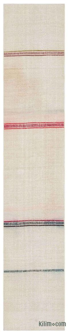 Vintage kilim rug handwoven in Turkey with hemp fiber. Turkish villagers produced hemp stalk until the 1960's when its production was prohibited together with its cousin, medical cannabis. These Anatolian rugs with modern appeal were mostly woven for drying fruits, to store wheat or as floor covers. This minimalistic beige rug measures 1'11'' x 10'1'' (23 in. x 121 in.).We professionally clean all our vintage rugs, but stains are a reminder of the rugs' history.