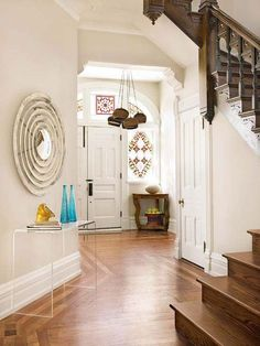| BHG Style Spotters | contemporary mirror wall art | acyrillic table in hallway with traditional staircase | modern residential interior designer ideas | home decor | entranceway | entry