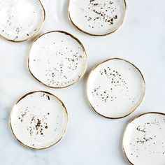 These pretty little porcelain dishes feature handmade ivory glaze splattered with genuine gold.