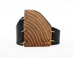 Plum tree wood, leather handmade cuff bracelet Wood: plum - surface of the wood is sanded, polished -length: 1 9/16, 4 cm -width: 1 3/8, 3,5 cm  Rings: brass  Leather: black  Closure: snap fasten at 5 3/4, 6 7/8, 7 7/8, 14,5, 17,5, 20 cm