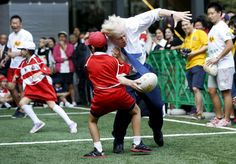 London's Mayor Boris Johnson collides with 10-year-old Toki Sekiguchi during a game of Street Rugby with a group of Tokyo children, outside the Tokyo Square Gardens building, October 15, 2015. T REUTERS/Issei Kato