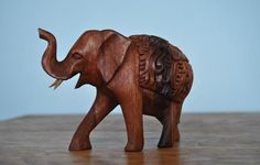 This charming elephant wood carving features intricate designs to make a visually enticing piece of art.