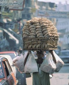Bread  vendor with bread heaped high in a basket and hanging in bags.