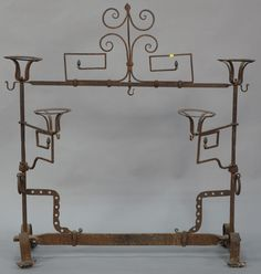 Iron fireplace frame with candle holders having swing arms and brass acorn finials, probably 18th to early 19th century.  ht. 48 in.; wd. 46 in.  Estimate: $250 - $450